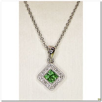This designer pendant was created by Dilamanti Designs. It is made in 18 karat white gold and has 4 Tsavorites stones totaling .27 carats surrounded by .08 carats total weight in diamonds. The bail will support many thinner type of chains. The chain shown is for display purposes only.