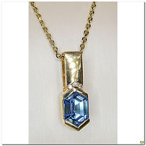 This designer piece was created in 14 karat yellow gold with a 7x10mm deep blue topaz with 3 diamonds totaling .05 carats. It has a large bail that will support almost any size chain. The chain shown is for display purposes only and is sold seperately.
