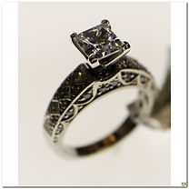 This vintage inspired engagement ring supports a 6mm center stone. Currently there is a cubic zirconia mounted for display purposes. It has 6 princess cut stones totaling .30 carat total weight. It also has an additional 32 round diamonds totaling .25 carats total weight.