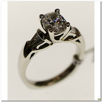 This designer engagement ring is created by Diana. It is made in platinum and will support approximately a one and a half carat oval center stone, currently it is set with a cubic zirconia for display purposes. It has four diamonds flanking the center stone with a total weight of .50 carats.
