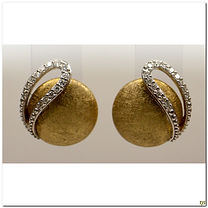 This designer earrings are created by Breuning.  It is made in 14 karat two-tone. A slight textured dome in yellow with a loop of diamonds totaling .17 carats total weight in SI clarity.