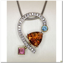 This substantial designer pendant was created by Frank Reubel. It was created in 14 karat white bold and has a large 10 carat Citrine a 1 caret pink topaz and a .02 carat blue zircon, with a half heart filled with diamonds. This is an Incredible piece of jewelry.