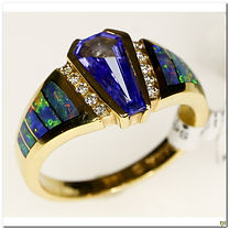 Custom designer, Kabana created this incredibly detailed inset Australian black opal ring surrounding a deep blue tanzanite, flanked with rows of diamonds.