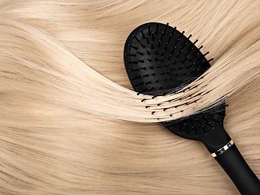 Closeup of Black hair brush lying on str