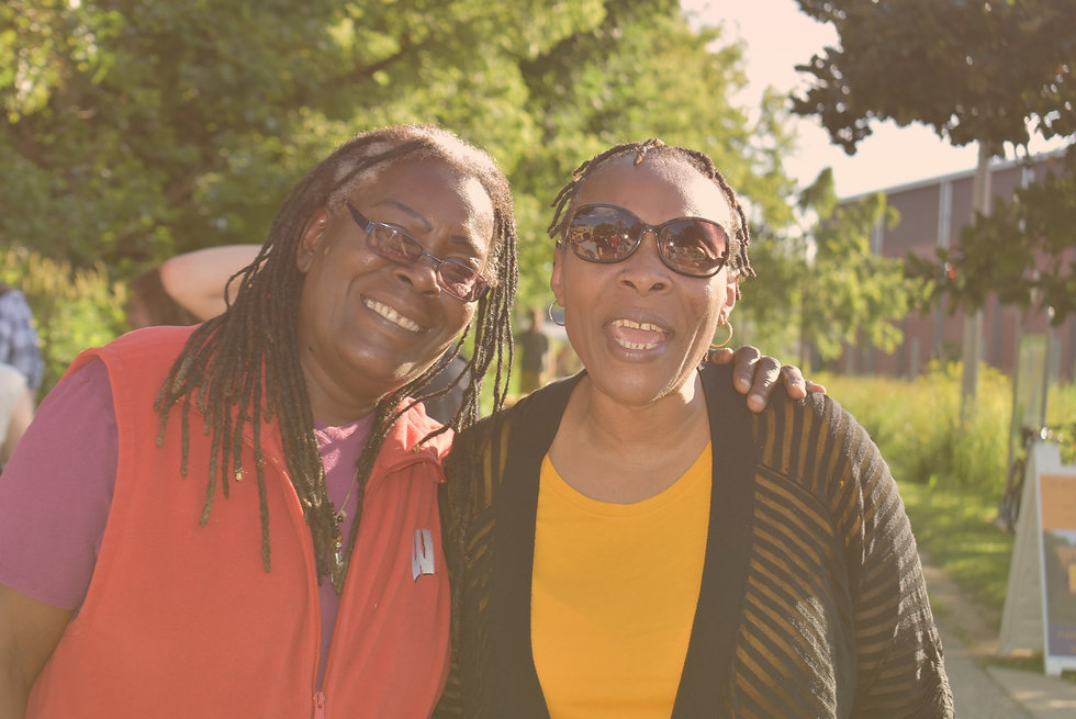 Two Yahara House colleagues, Kathy and Fee, smiling at a community event outdoors.