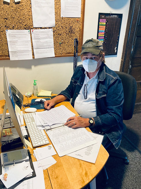 Colleague, Dave, wearing a mask and ball cap at the reception desk.