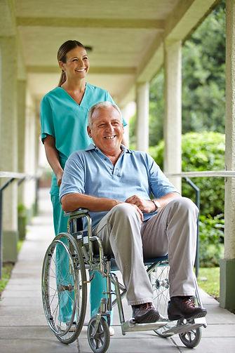 Senior man in wheelchair with nurse in t