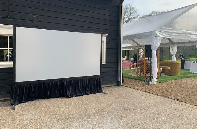 A large projection screen rental erected in front of a barn for an outdoor wedding reception under a clear tent.