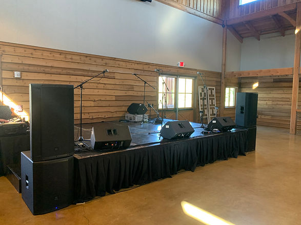 Three-way speakers on top of JBL subwoofers at a stage for a band performance during a wedding reception.