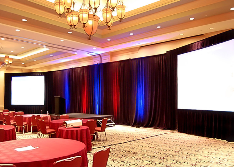 Conference with black drapery including red and blue uplighting setup at a hotel.