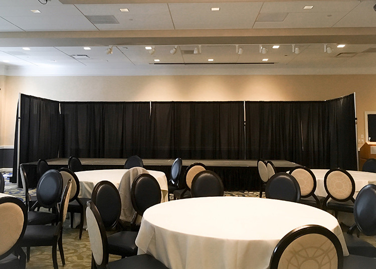 A corporate conference with black pipe and drape surrounding the stage.