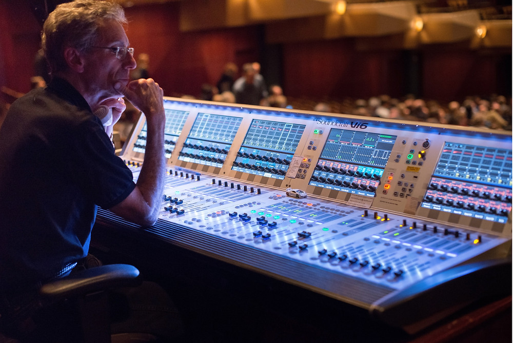 A man mixing live sound on a mixing console.