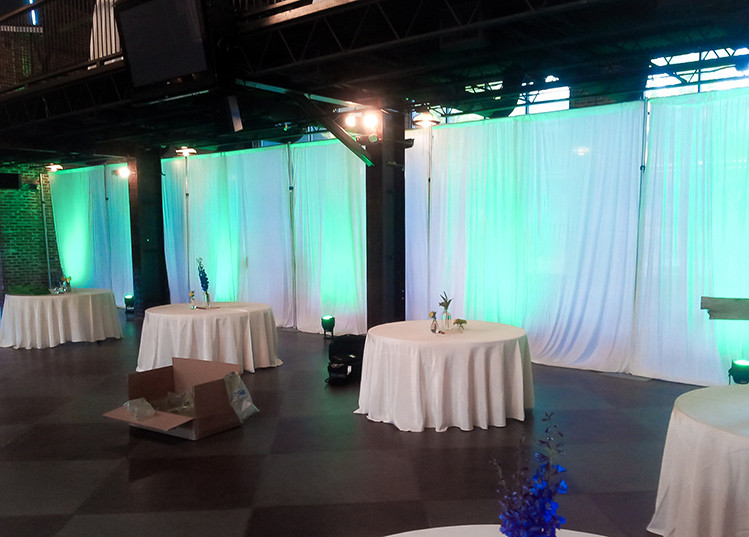 A wedding reception with white pipe and drape with lime green uplighting.