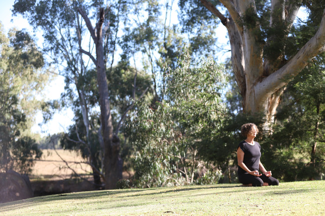 Meditative yoga pose on riverbank