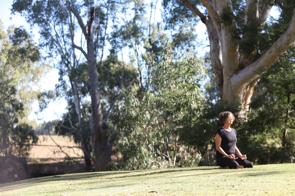 Meditative yoga pose on riverbank