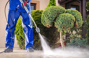 Caucasian Worker in His 30s with Pressure Washer Cleaning Residential Driveway. Garden and