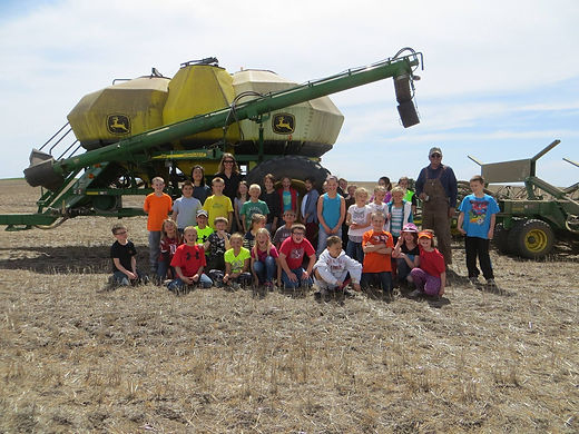 Direct seed producer in front of his combine surrouded by children after a field trip in the field planting garbonzo beans