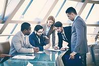 Fünf Manager stehen um einen Tisch und besprechen ein Vorhaben. Sie tragen Anzüge. Drei tragen eine Krawatte. In der Mitte steht eine Frau. Führungskräfte lernen eine Sprache.