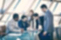 Fünf Manager stehen um einen Tisch und besprechen ein Vorhaben. Sie tragen Anzüge. Drei tragen eine Krawatte. In der Mitte steht eine Frau. Vielleicht lernen sie Sprachen