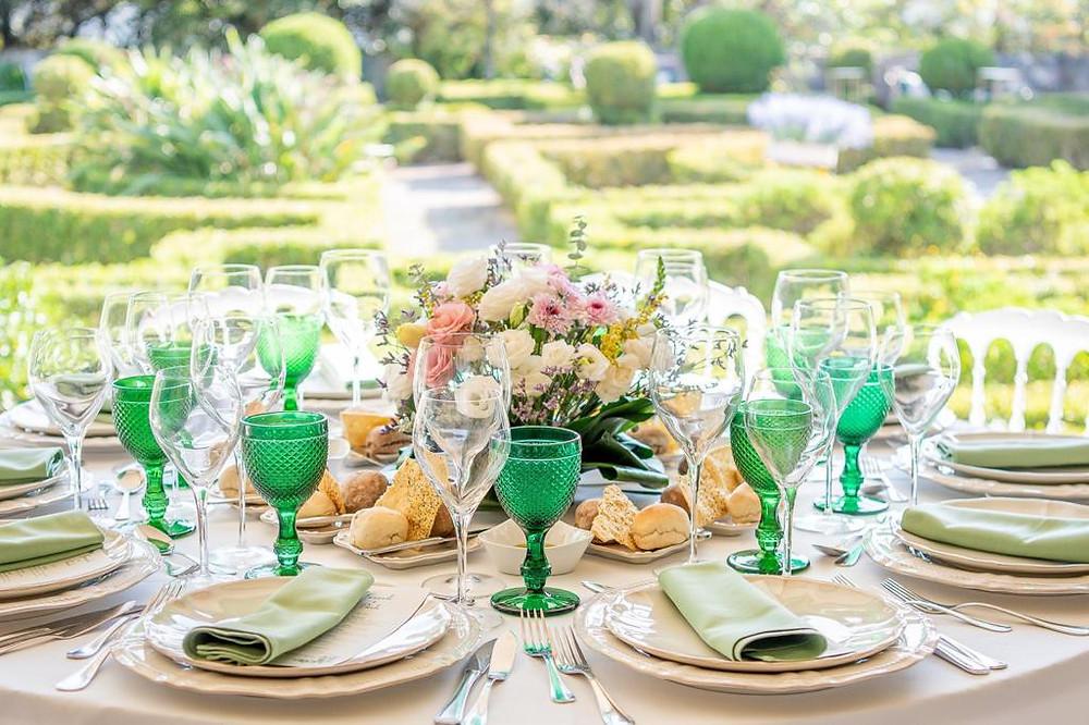 Mesa redonda de casamento com copos verdes e guardanapos verdes no terraço da Quinta do torneiro