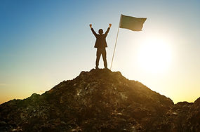 Image of man on top of hill with success flag.