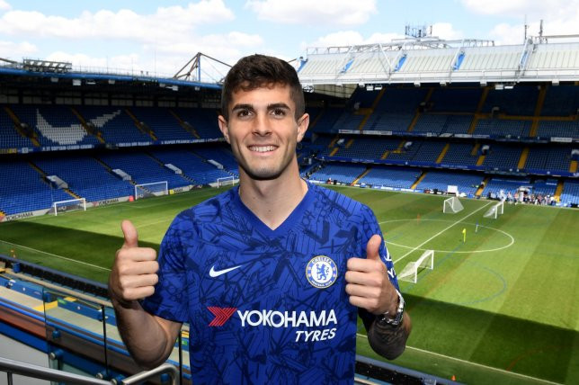 Christian Pulisic smiles for the camera after signing for Chelsea