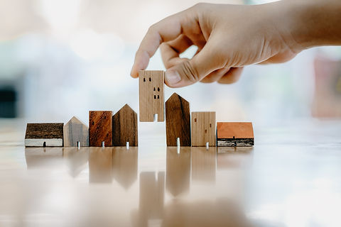 Hand choosing mini wood house model from