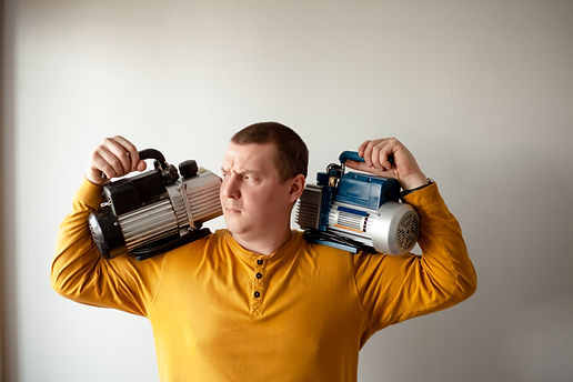 A strong man holds two vacuum pumps for