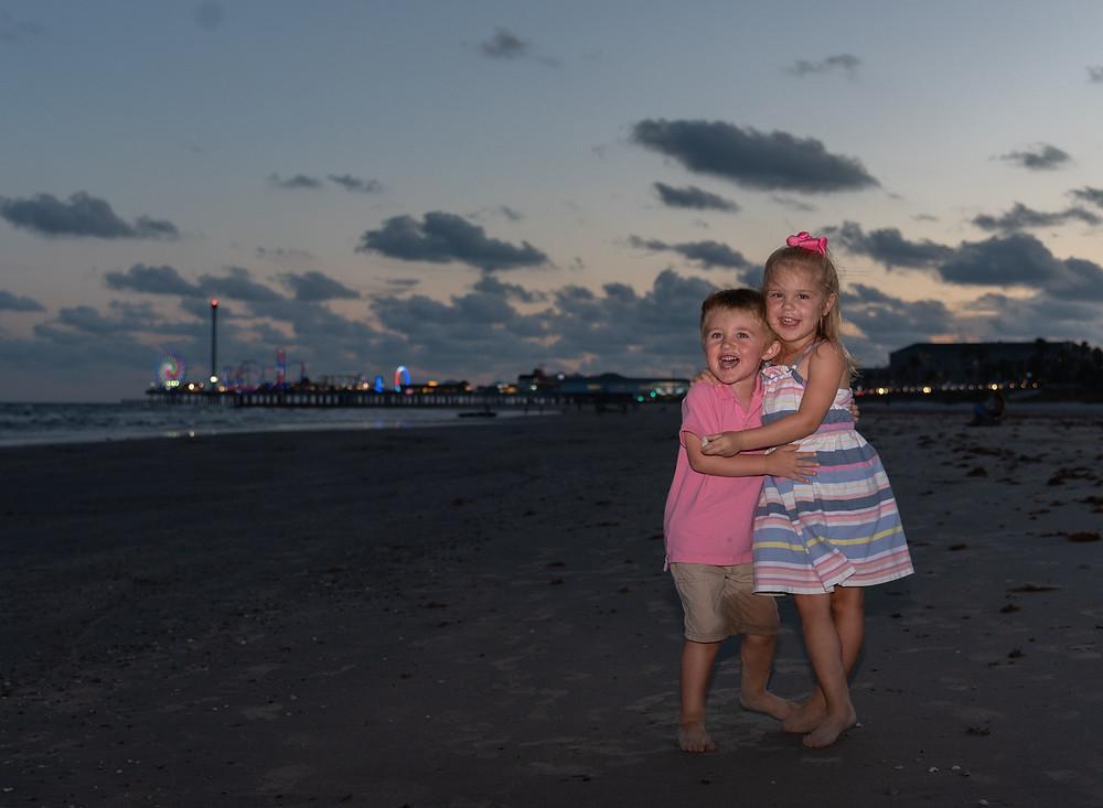 Peyton & Kasen at Galveston Beach with Pleasure Pier in the background