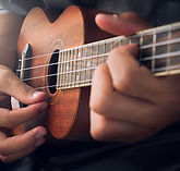 A man playing ukulele in close up view..
