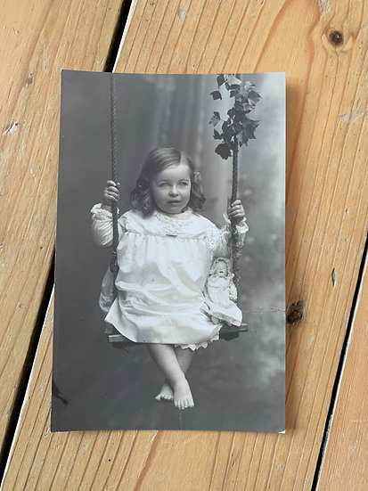 Pretty Girl on Swing with a Doll