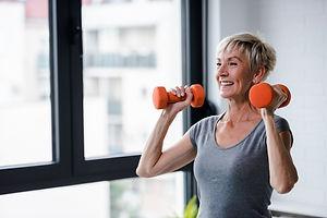 Portrait of senior woman lifting dumbbel
