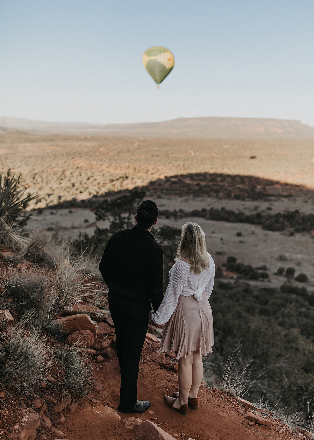 Couple on mountain looking at hot air balloon