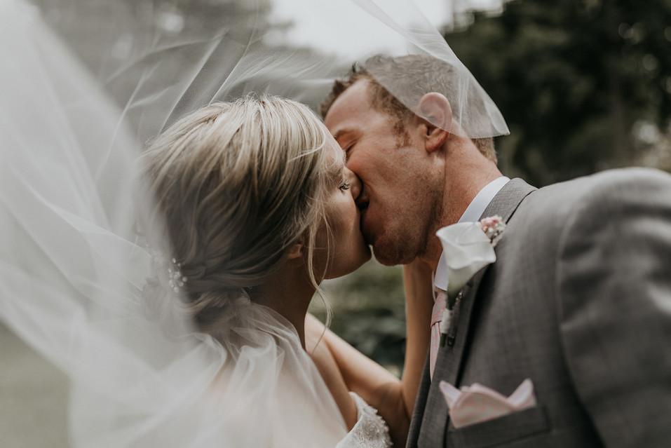 wedding couple kissing under veil