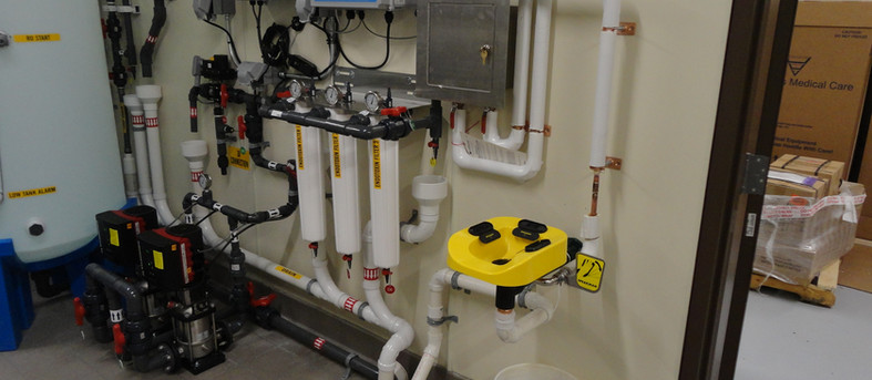Kidney dialysis water treatment equipment room with emergency face wash, mixing valve, floor sink and related equipment