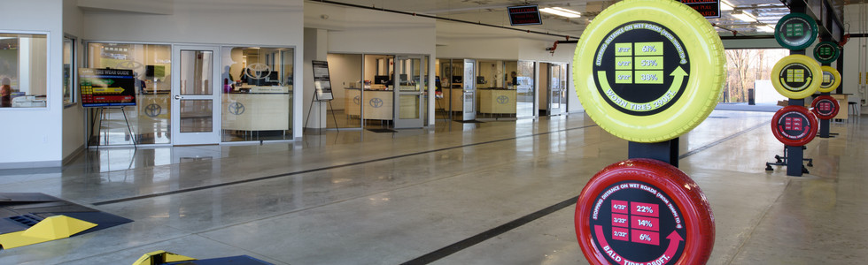 Trench drain system in auto dealership vehicle drop-off area designed to maintain dry floors in pedestrian traffic areas