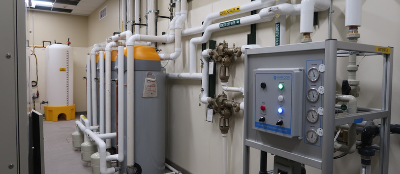 High efficiency water heaters, twin reduced pressure zone backflow preventers and related water treatment equipment