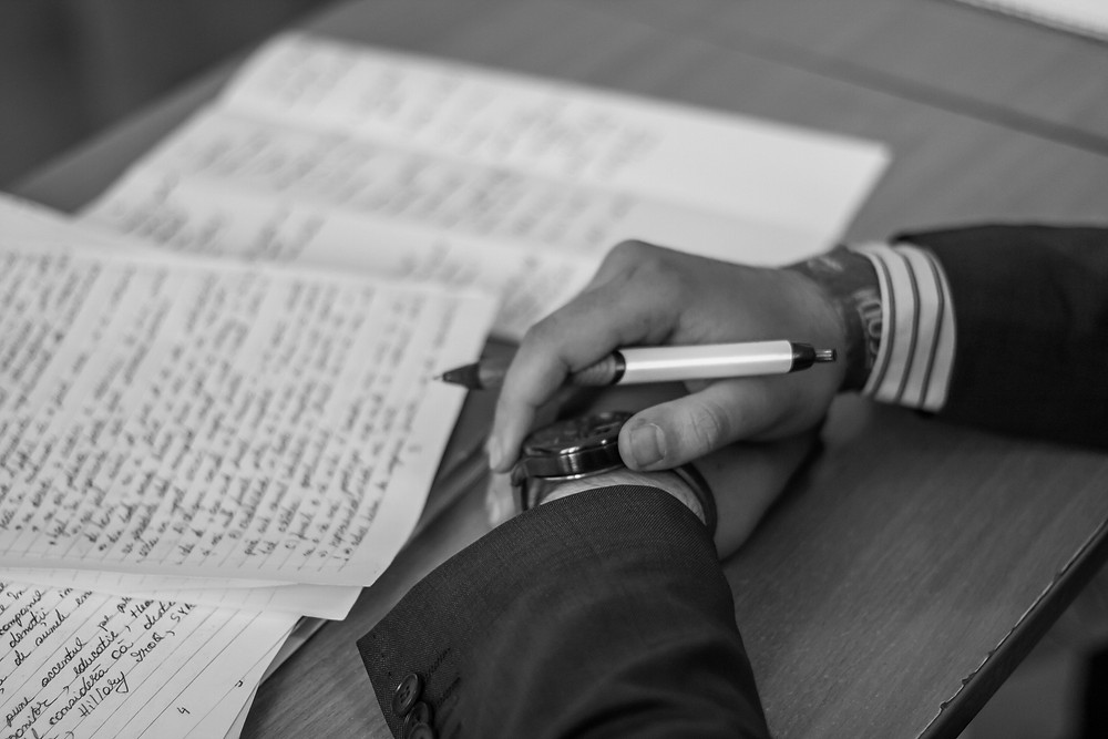 Two hands next to a pile of papers. One hand is grasping a pen and a watch.