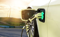 Electric car or EV car charging in station on blurred of sunset with wind turbines in fron