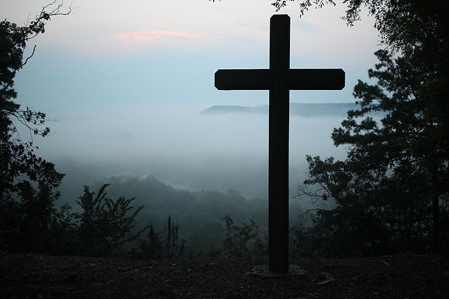 Cross in front of cloudy moutain