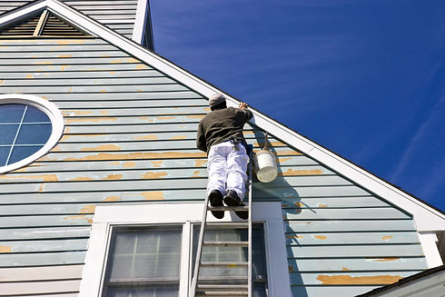 A contractor or painter on a ladder doin