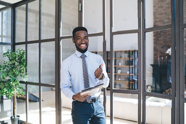 Portrait of black smiling agent standing