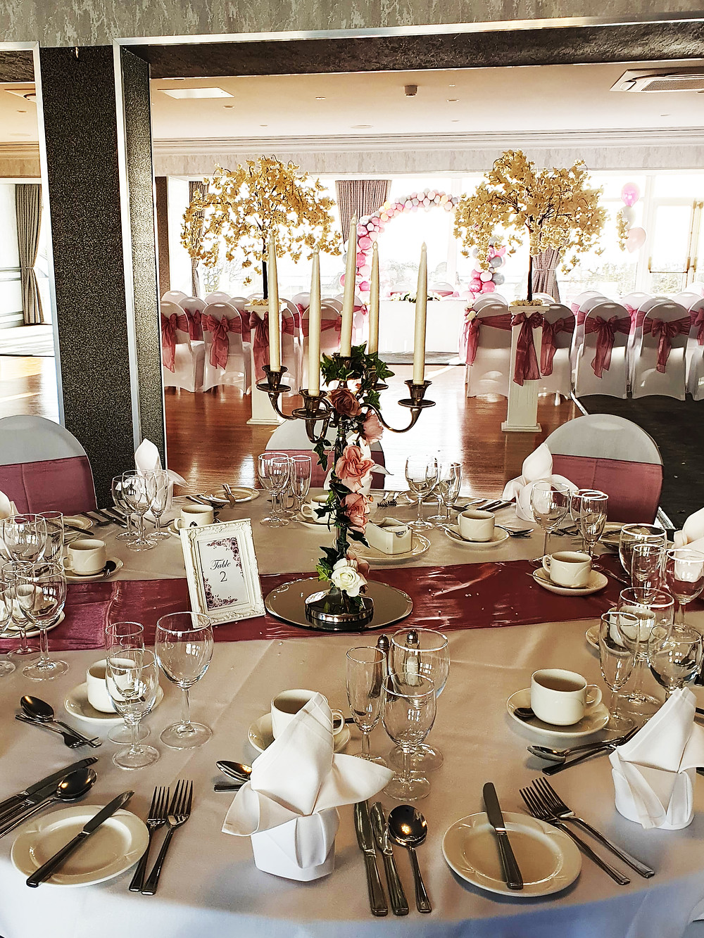 TABLE NUMBERS TABLE RUNNERS CANDELABRAS TRAILING IVY ROSES NAPKINS CHAIR COVERS MAUVE CHAIR SASHES MAUVE PINK BLOSSOM TREES COLUNMS BALLOON ARCH GLASSES CUPS KNIVES FOLKS RUSTIC WEDDING CLASSIC WEDDING LOOK