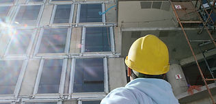 man with yellow hard hat looking up at building