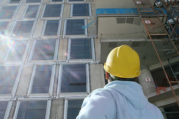 Worker looking at building covered by construction insurance in Sydney