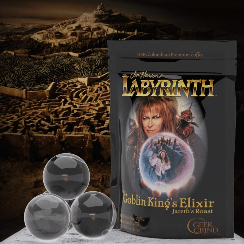 """A bag of Goblin King's Elixir coffee, with cover are showing Jareth and """"Jim Henson's Labyrinth"""" above him. Crystal obs sit beside the bag."""