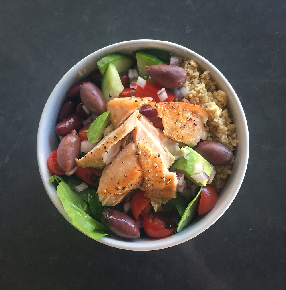 salmon, olives, couscous salad in a bowl