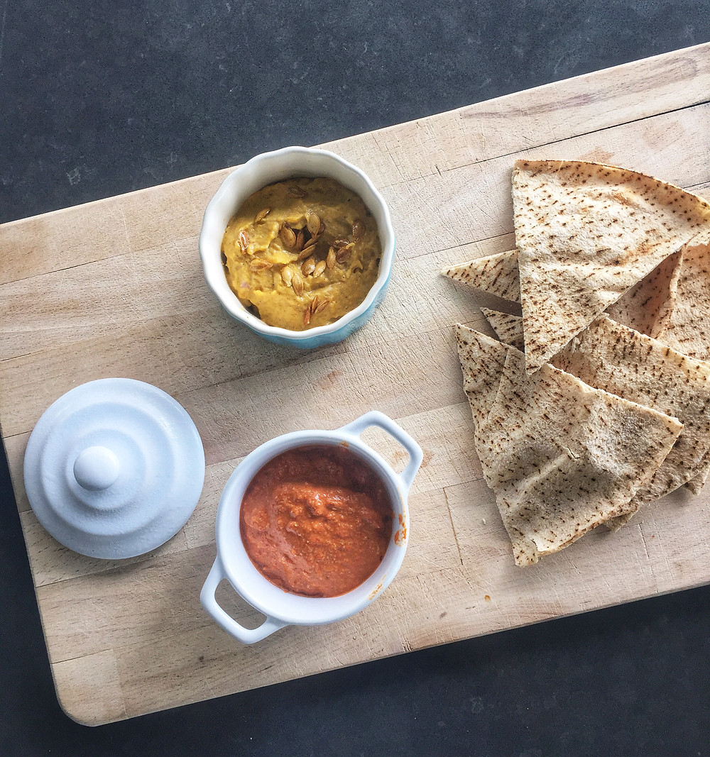 pumpkin dip and capsicum dip with pita on wooden board