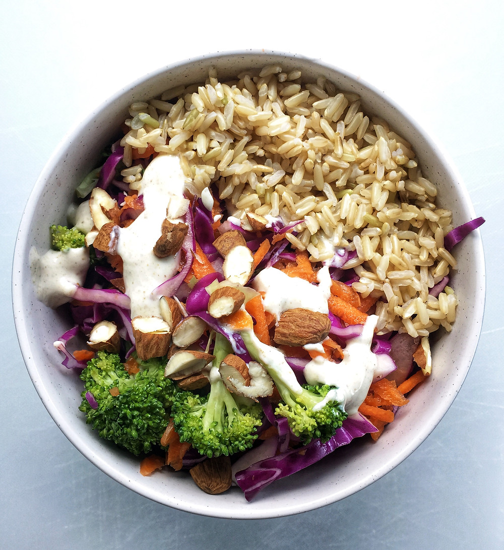 bowl with brown rice, broccoli, red cabbage, carrot, almonds and yoghurt dressing