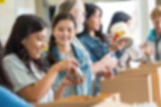 Peple volunteering unpackng boxes of dnated food